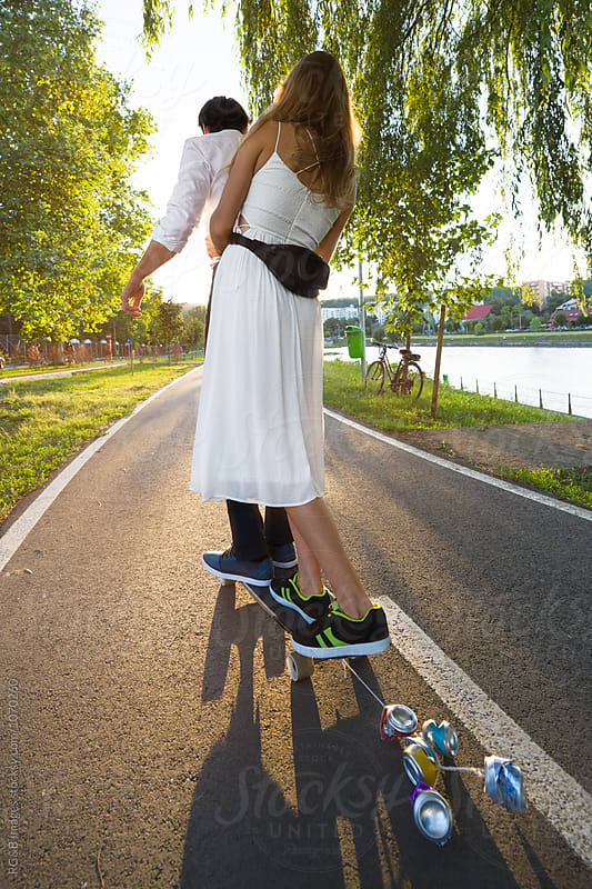 Just married couple riding a longboard by RG&B Images for Stocksy United