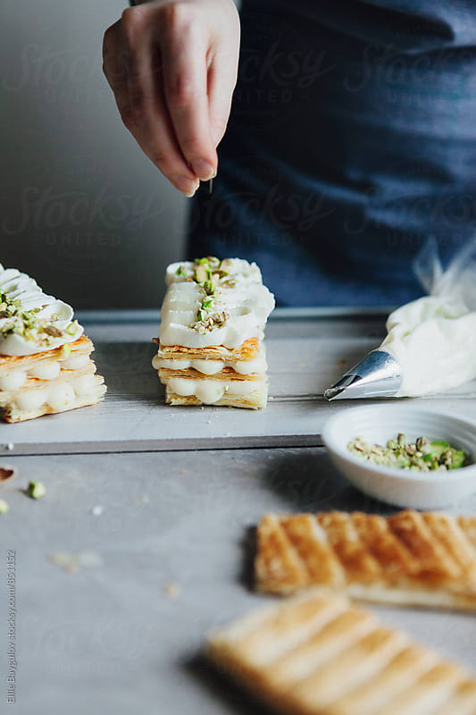 Woman preparing vanilla millefeuille by Ellie Baygulov for Stocksy United