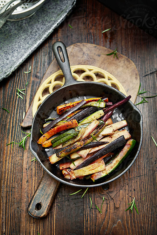 Mixed roasted vegetables in a skillet by James Ross for Stocksy United