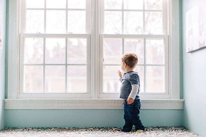 Cute young boy standing on a window seat looking out a window by Jakob for Stocksy United