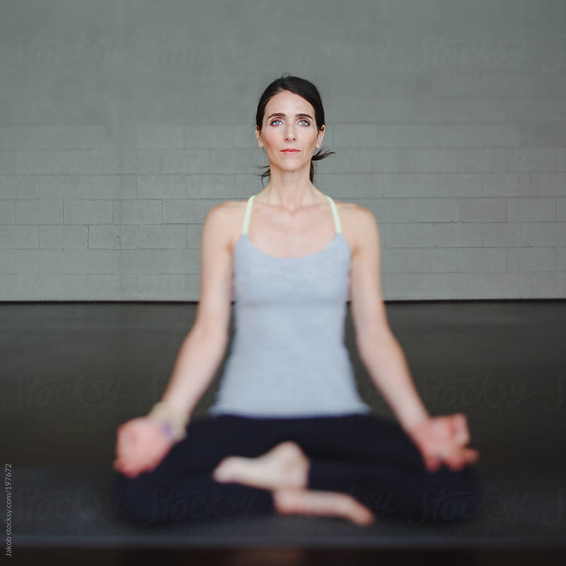 A beautiful woman practicing yoga in a studio by Jakob for Stocksy United