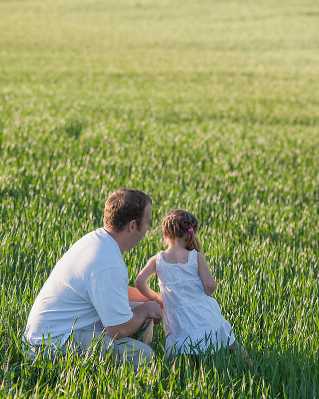 Father and young daughter look out over agricultural field by Brian McEntire for Stocksy United