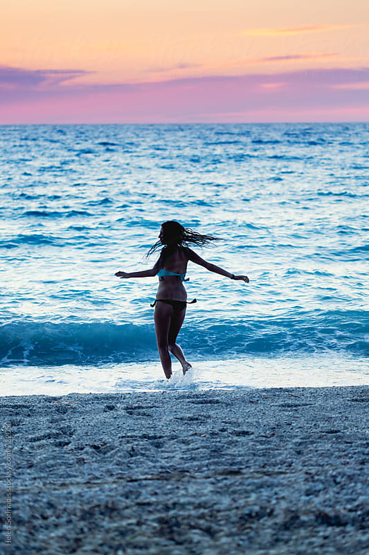 Young Woman Spins at the Beach at Twilight by Helen Sotiriadis for Stocksy United