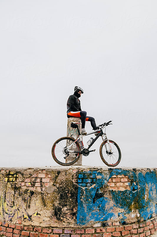 Mountain Bike Rider Resting Over Grunge City Viewpoint by VICTOR TORRES for Stocksy United