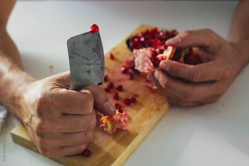 Man holding knife with pomegranate seed on it  by Jovo Jovanovic for Stocksy United