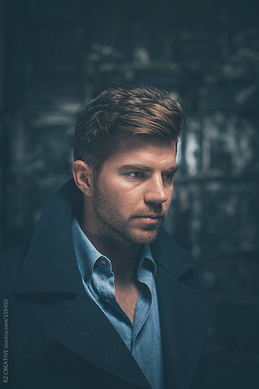 Portrait of a man with great hair wearing a blue dress shirt and peacoat. by RZ CREATIVE for Stocksy United