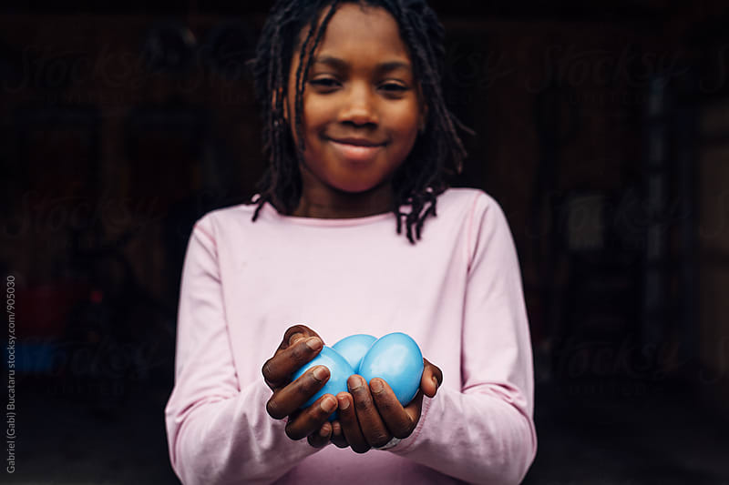 Black girl in pink shirt holding pastel blue Easter eggs by Gabriel (Gabi) Bucataru for Stocksy United