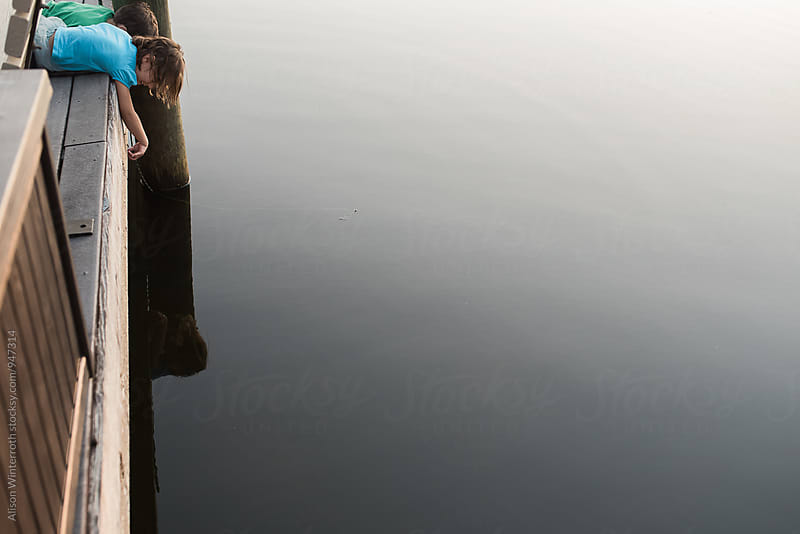 Children Look Off The Edge Of A Calm Lake by Alison Winterroth for Stocksy United