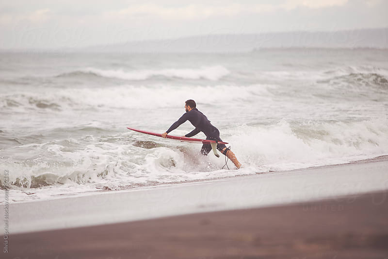 Surfer going into the water for a surf session by Silvia Cipriani for Stocksy United