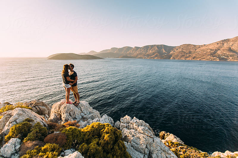 couple kissing on a rocky outcrop overlooking a calm sea at sunset in Kalymnos, Greece by Micky Wiswedel for Stocksy United