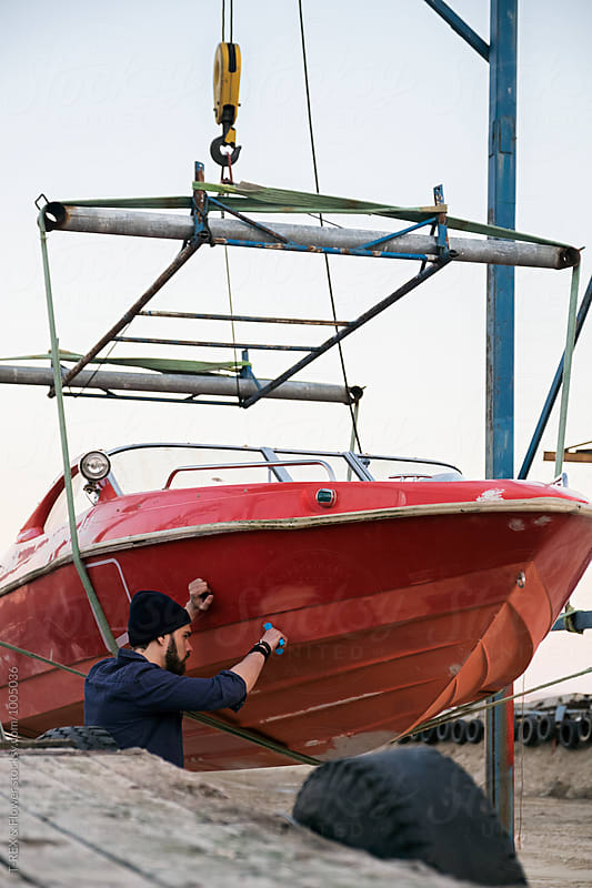 Side view of bearded painter restoring red boat with brush by Danil Nevsky for Stocksy United