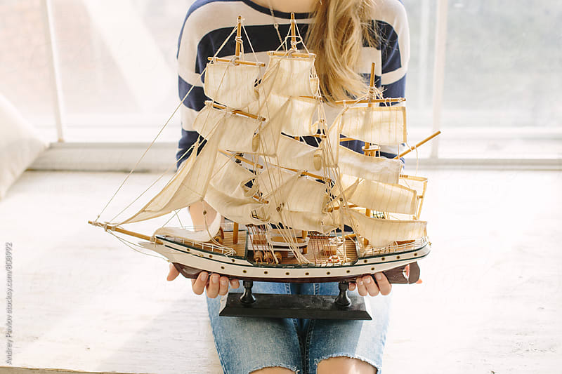Woman holding warship miniature by Andrey Pavlov for Stocksy United