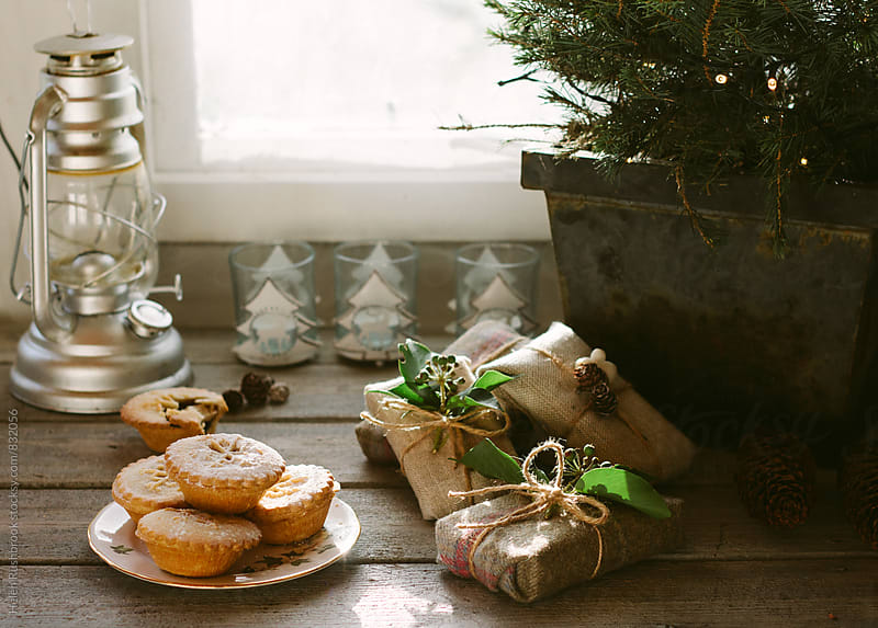 Mince pies and Christmas gifts under a Christmas tree. by Helen Rushbrook for Stocksy United