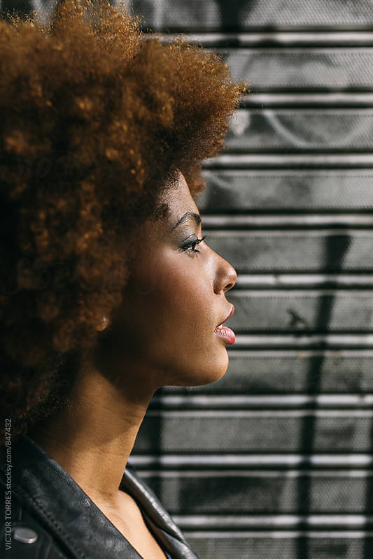 Beautiful Afro Woman over a Black Background by Victor Torres for Stocksy United