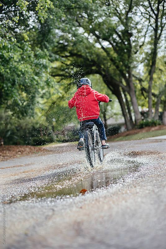 Boy rides his bike through a puddle and makes a nice splash by Cara Dolan for Stocksy United