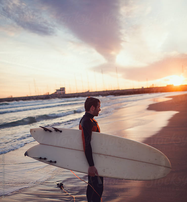 Portrait of a surfer with board on sunrise by Leandro Crespi for Stocksy United