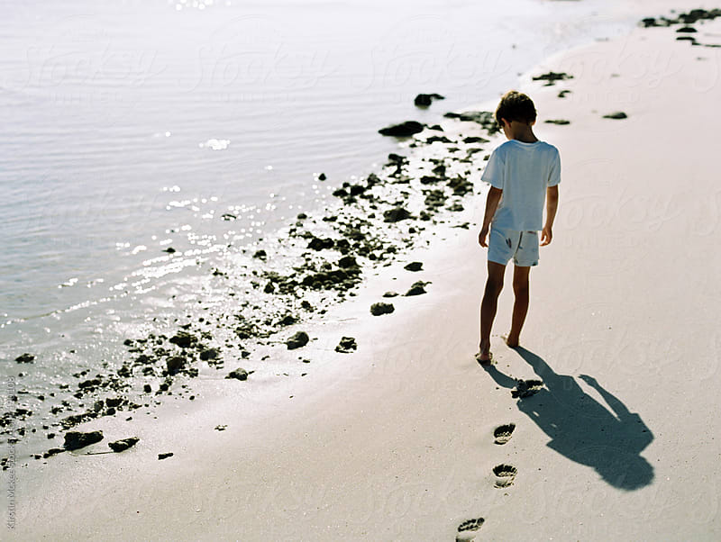 Boy walking on beach in early morning by Kirstin Mckee for Stocksy United