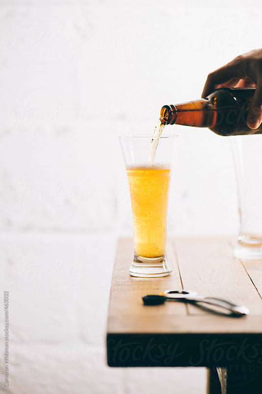 Bottled beer poured into a Pilsner glass by Cameron Whitman for Stocksy United
