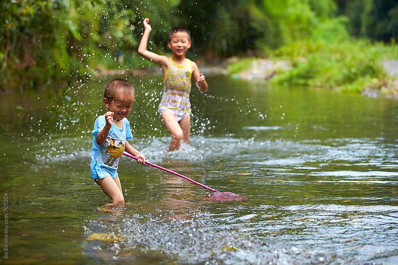 happy asian kid having fun in the stream by Bo Bo for Stocksy United