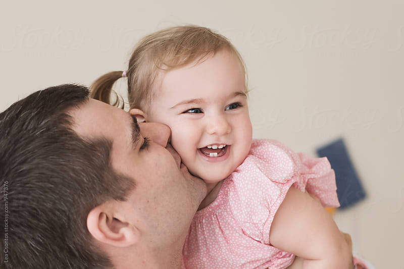 Father holding and kissing her daughter by Lea Csontos for Stocksy United
