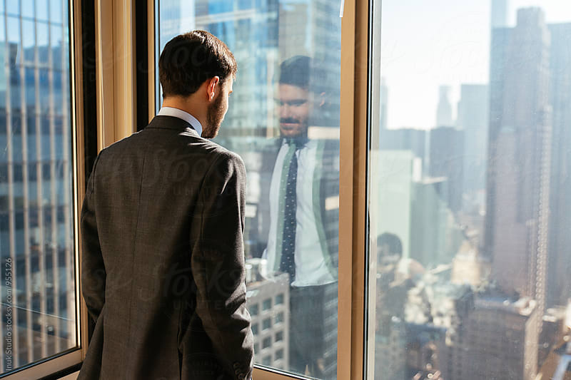 Businessman looking through window at city from the office by Inuk Studio for Stocksy United