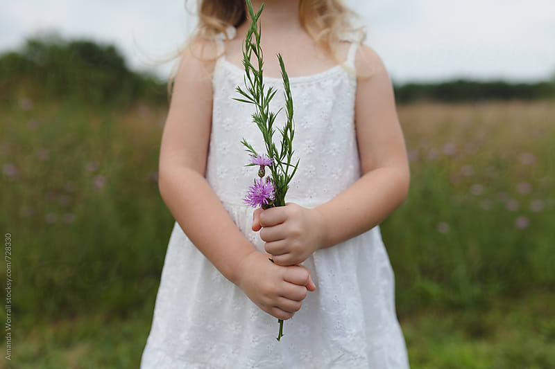 Anonymous young girl holding a bouquet of wildflowers by Amanda Worrall for Stocksy United