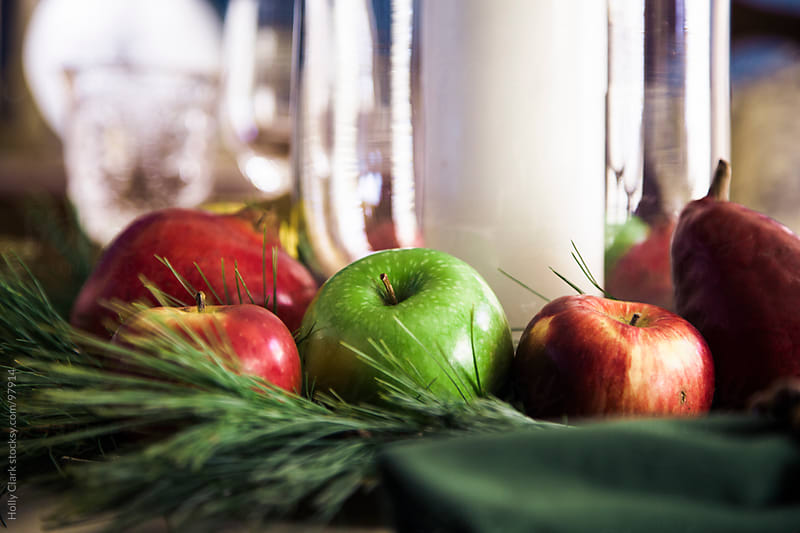 Apples, pears and pine needles make up a table centerpiece. by Holly Clark for Stocksy United