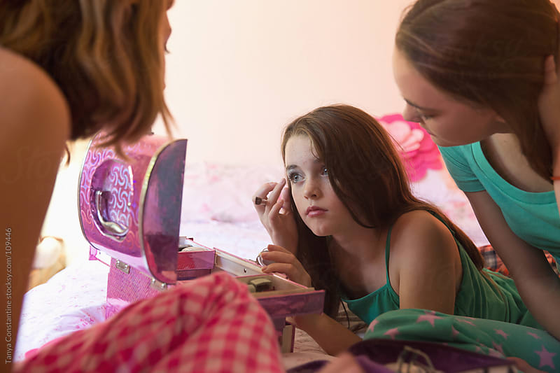tweens putting on make-up by Tanya Constantine for Stocksy United