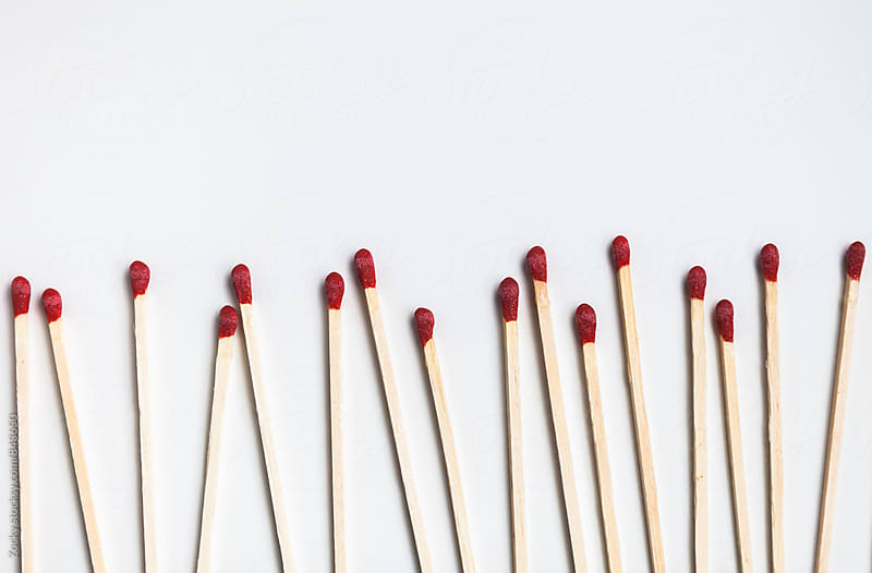 Matches in a row on white background by Zocky for Stocksy United