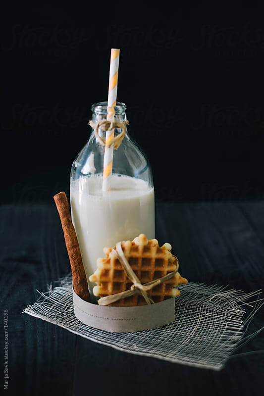 Fresh waffle, bottle of milk and cinnamon on wooden black table.  by Marija Savic for Stocksy United