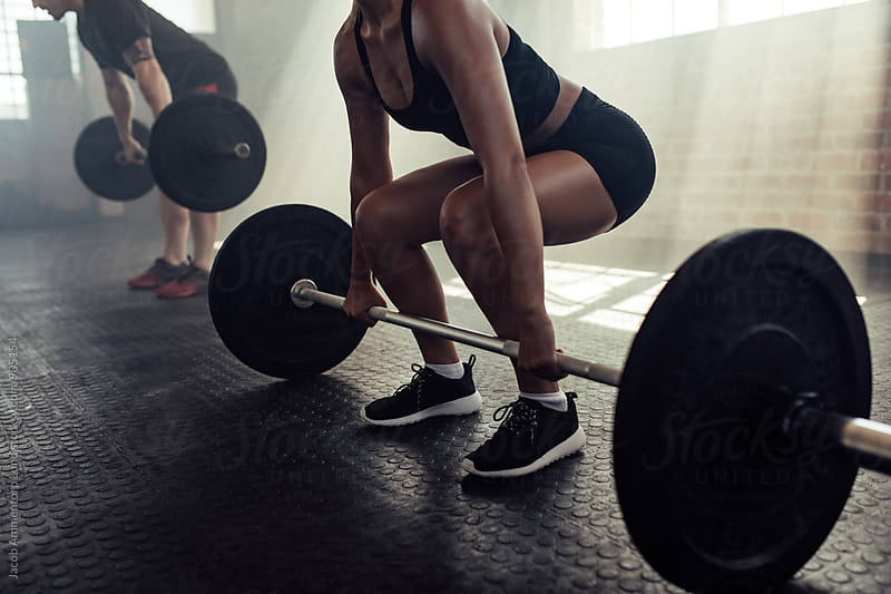 Woman lifting barbell at gym by Jacob Lund for Stocksy United