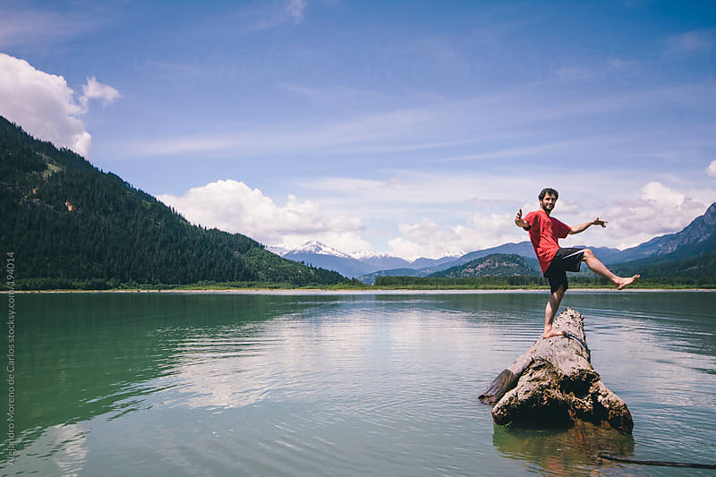 Young man balancing on a floating log in a lake by Alejandro Moreno de Carlos for Stocksy United