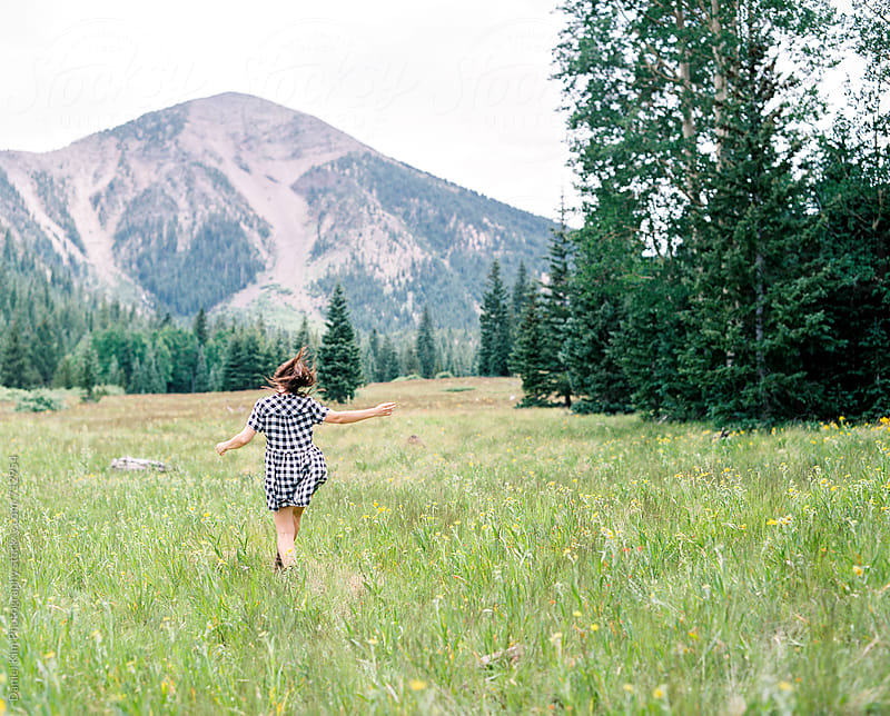 Woman jumping in meadow by Daniel Kim Photography for Stocksy United