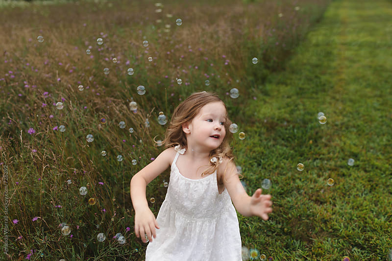 Girl in motion, chasing bubbles by Amanda Worrall for Stocksy United