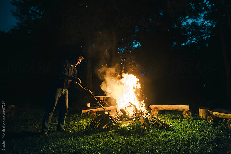 Man Tending a Campfire by Stephen Morris for Stocksy United