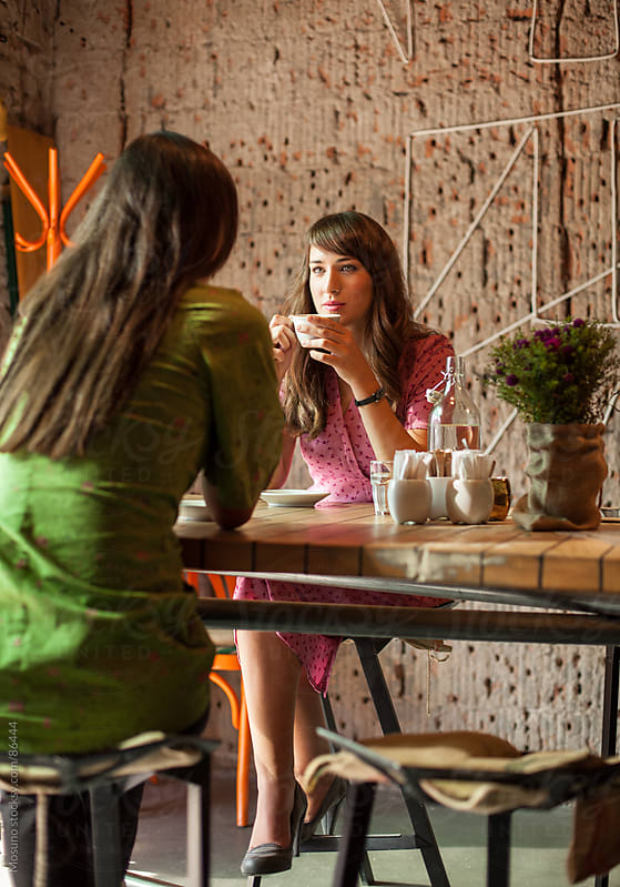 Two Girlfriends Sitting in a Coffee Shop by Mosuno for Stocksy United