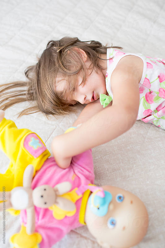 Baby girl lying on the bed with her doll by michela ravasio for Stocksy United