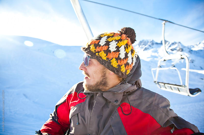 Young snowboarder sitting in a chairlift on a sunny day in the mountains by Ivo de Bruijn for Stocksy United