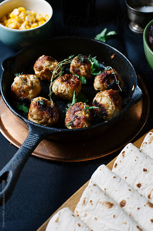Meatballs in a cast iron skillet on a table with side dishes. by Darren Muir for Stocksy United