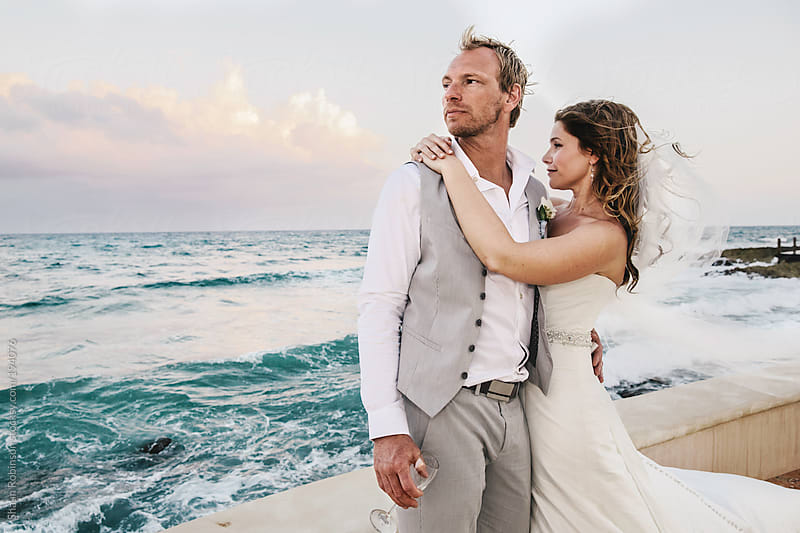 A bride and groom looking at the ocean after the ceremony by Shaun Robinson for Stocksy United
