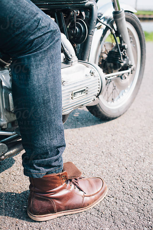 Close up of a motorsyclists boot and jeans while sitting on his motor by Ivo de Bruijn for Stocksy United