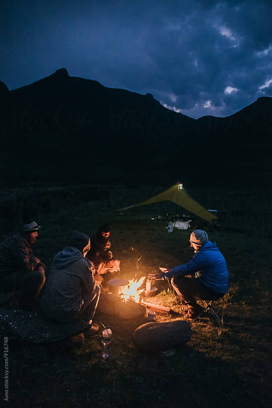 hiker outdoorsmen sitting around a camp fire at night by Micky Wiswedel for Stocksy United
