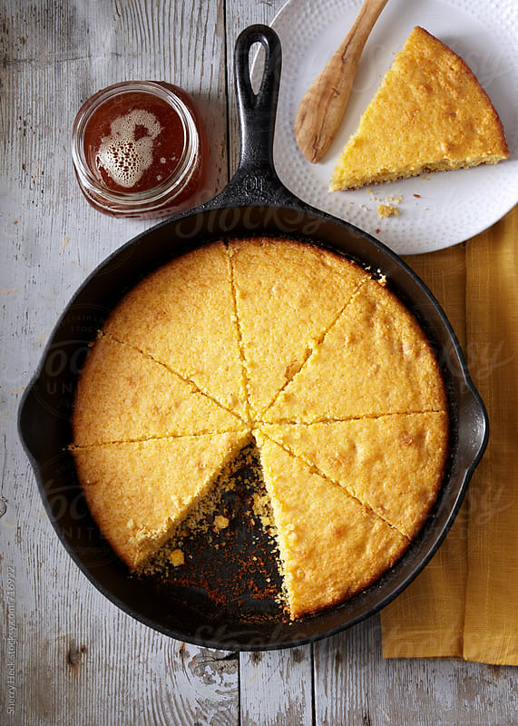 Cornbread in iron skillet cut into pie wedges overhead with honey by Sherry Heck for Stocksy United