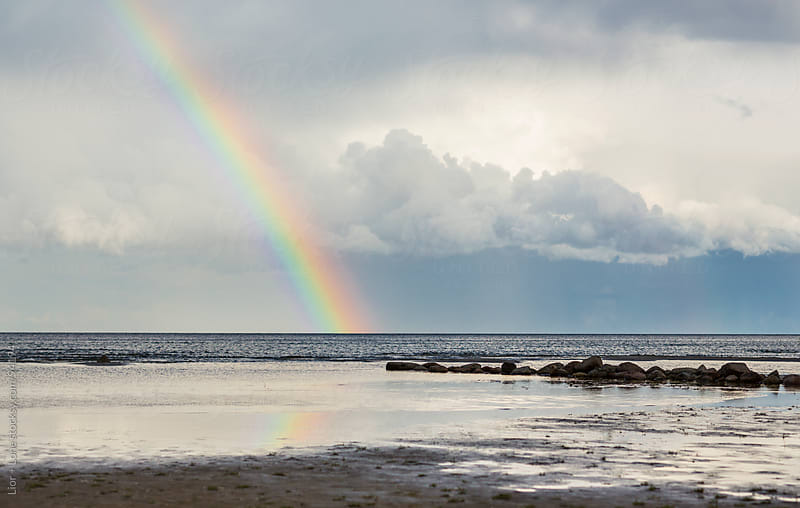 Rainbow over shallow beach under stormy sky by Lior + Lone for Stocksy United