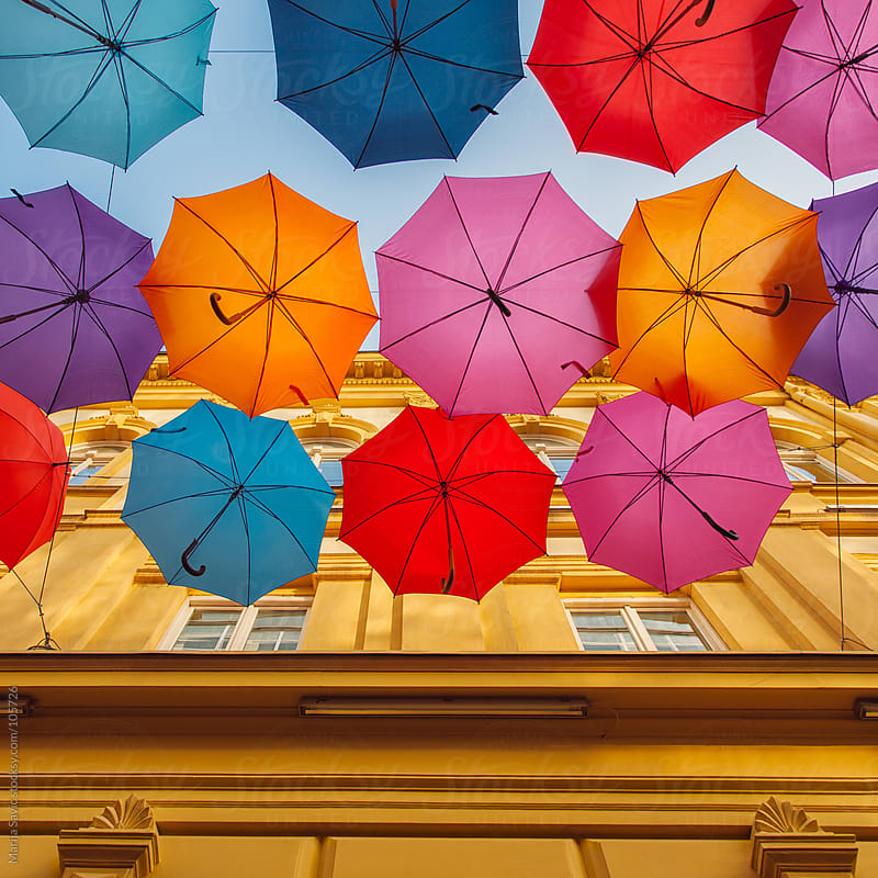 Colourful umbrellas hanging above the street. by Marija Savic for Stocksy United
