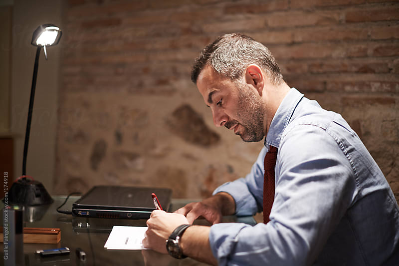 handsome business left-handed man writing by Guille Faingold for Stocksy United