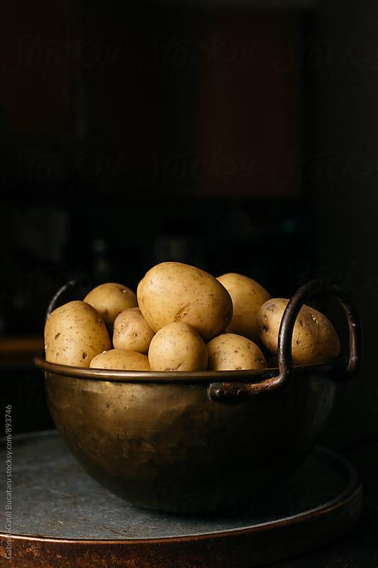 Brass bowl with potatoes by Gabriel (Gabi) Bucataru for Stocksy United