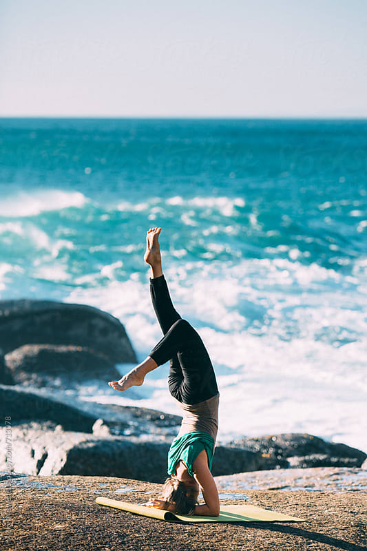 Young fit woman doing yoga at a rocky beach by Micky Wiswedel for Stocksy United