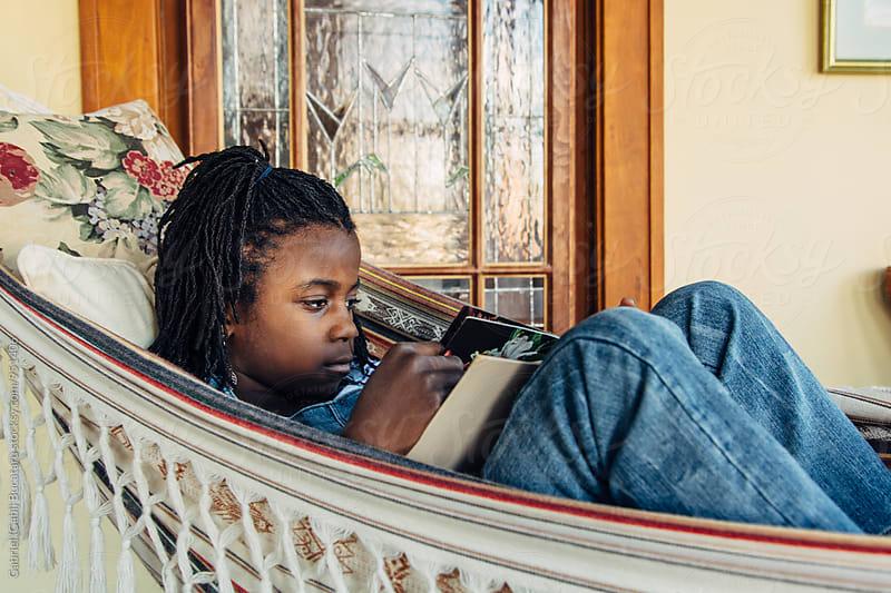 African American girl reading a book by Gabriel (Gabi) Bucataru for Stocksy United