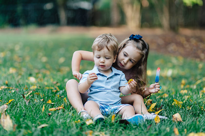 Sister and brother sitting in grass sharing a popsicle by Jakob for Stocksy United